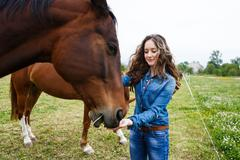 Young beautiful girl feeding a horse - stock photo
