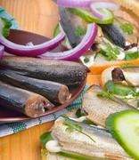 Sandwich with sprats and green cucumber - stock photo
