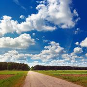 Rural landscape with road and clouds Stock Photos