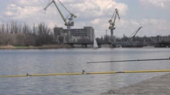 Fishing rod on river against  background of shipbuilding cranes Stock Footage