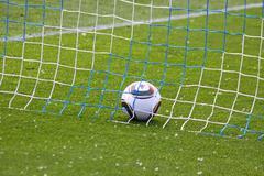 Soccer ball inside the net on the green grass field Stock Photos