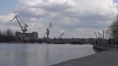 Shipbuilding cranes on background of factory buildings view from the water 4k Stock Footage
