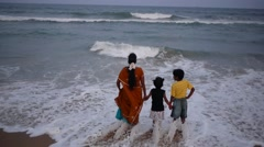 A family plays with the waves on Marina beach,Chennai,India Stock Footage