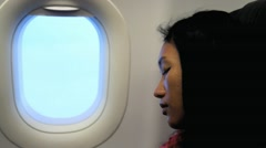Woman sleeping in a flying aircraft next to the window with noise of engine Stock Footage
