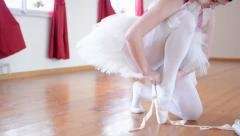 Young ballerina puts on ballet shoes and ballerina ties shoes Stock Footage