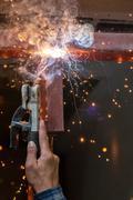 Stock Photo of welding steel with spread spark lighting smoke