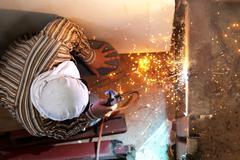 welding steel with spread spark lighting smoke - stock photo