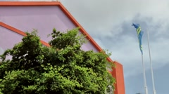 Aruba Oranjestad 027 national flag next to a violet gable of modern building Stock Footage