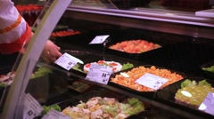 Assortment of salads on display cabinet in supermarket. Female hands saleswoman Stock Footage