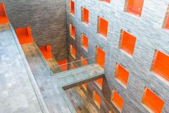 Interior modern building with several floors and orange painted passages Stock Photos