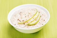 Oatmeal porridge with apple slices and cinnamon - stock photo