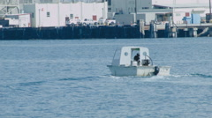 SMALL BOAT WITH UNRECOGNIZABLE CAPTAIN MAKES A TURN IN THE HARBOR. Stock Footage