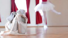 Detail ballet shoes - ballerina dancing in the background - interior - red curta Stock Footage