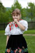 Little girl in traditional costume with flowers - stock photo