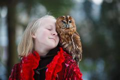 Cute girl with little owl - stock photo