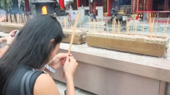 Young woman lights a stick in a Buddhist monastery Stock Footage