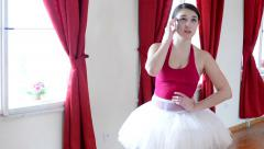 Young attractive ballerina phone - hall - red curtain Stock Footage