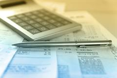 Calculator and the financial report blue toned.Financial accounting. Stock Photos