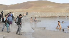 People bathe in El Tatio geothermal water pool in San Pedro de Atacama, Chile. Stock Footage