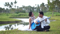 Young man serenades sweetheart with guitar sitting - stock footage
