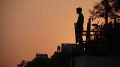 Man standing on ghat  at sunset,Varanasi,India - stock footage