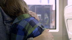 Closeup Of A Mother Patting Her Son's Back As He Sleeps On The Train Stock Footage