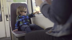 Little Boy Plays With Dino Toy On The Train, His Mother Takes A Photo Of Him(4k) Stock Footage