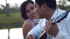 Young man serenades sweetheart with guitar - stock footage