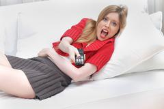 Young girl holding remote control and screaming Stock Photos