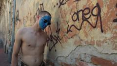 Man with blue painted face walking through ruined part of town Stock Footage