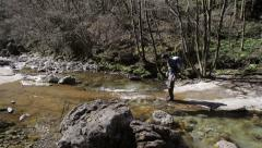 Trekking - crossing the river, near the waterfall - stock footage