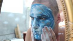 Washing his blue painted face in front of the mirror 1/2 Stock Footage