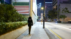 Following alone girl on the night street, police car drive side away Stock Footage
