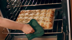 Taking fresh hot cross buns from gas oven in slow motion 4K - stock footage