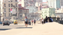 Tourists and locals enjoy the malecon as Cuban cars zip by. Stock Footage