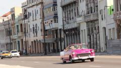 Bright pink classic American car drives by with tourists in Havana, Cuba Stock Footage