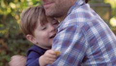 Blond little boy hugging young father Stock Footage