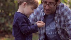 Little Blond Boy holding and looking at Fall leaf with his Father Stock Footage
