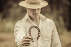 Lucky Farmer Holding a Horseshoe Stock Photos