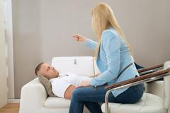 Female Psychiatrist Hypnotizing Patient Lying On Couch Stock Photos
