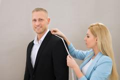 Young Female Tailor Takes Measures Of Man With Measuring Tape Stock Photos