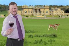 Stock Photo of Businessman holding glass of wine with beautiful villa in background