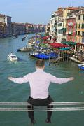 Businessman sitting on light metal girder beam with view of Venice, Italy in Stock Photos