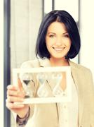 businesswoman holding hourglass - stock photo