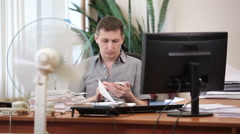 Employee calling cellphone on working place with cooling fan in office space - stock footage