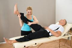 Young Female Instructor Helping Man For Doing Exercising - stock photo