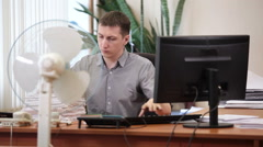 Employee arranging paper documents, turning on cooling fan in office space Stock Footage
