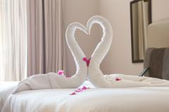 Two Swans Made Of Towels Forming Heart Shape On Bed - stock photo