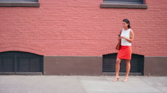 Woman looks at her phone in the city as her boyfriend shows up to give her a hug Stock Footage