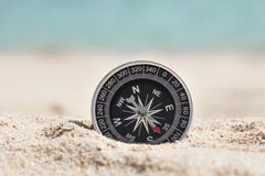 Close-up Photo Of Black Compass On Sand - stock photo